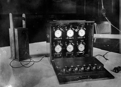 An electro-mechanically controlled briefcase containing six stopwatches, as used in the 1920s.