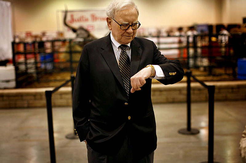 Warren Buffet standing looking at his Rolex Day-Date President